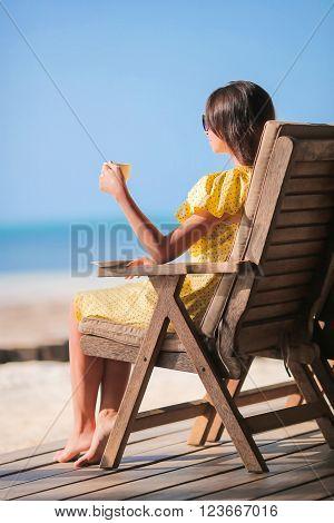 Young woman drinking coffee enjoying beach view