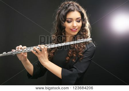 Beautiful young woman with flute on dark background