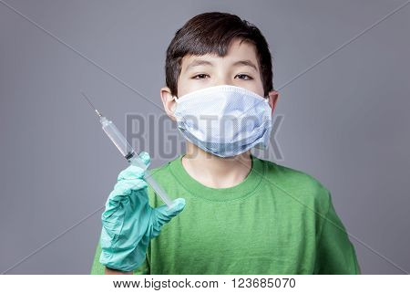Boy with syringe plays doctor. A young boy is playing doctor by holding a syringe and wearing a mask.