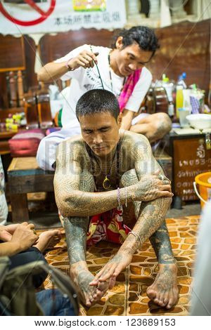 WAT BANG PHRA, THAILAND - MAR 18, 2016: Unidentified monk makes traditional Yantra tattooing during Wai Kroo Master Day Ceremony in Bang Pra monastery, about 50 km west of Bangkok.