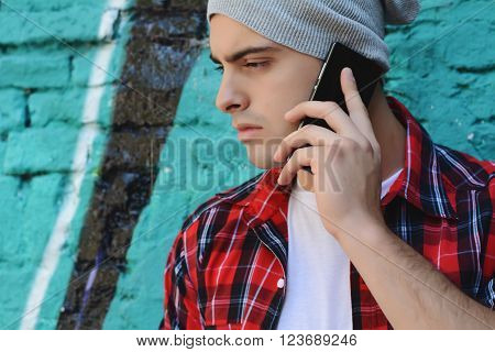 Portrait of young handsome man talking on the phone outdoors
