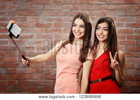 Two teenager girls making photo by their self with mobile phone on brick wall background