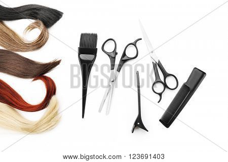Hairdresser's scissors with tools and varicolored strands of hair, isolated on white poster