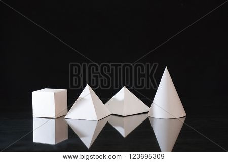 Geometry concept. Set of various paper shapes on dark background