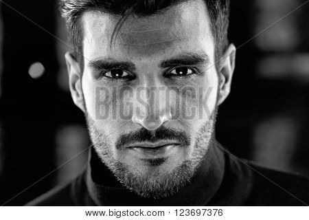 Black and white closeup photo of handsome young man looking at camera.