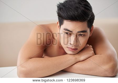 Contemplating shirtless Vietnamese man leaning on table