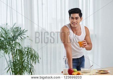 Smiling fit Vietnamese man standing at table with healthy breakfast