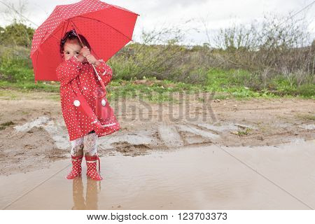 Baby girl dressed with dotted raincoat and umbrella a typical rainy and windy day of autumn