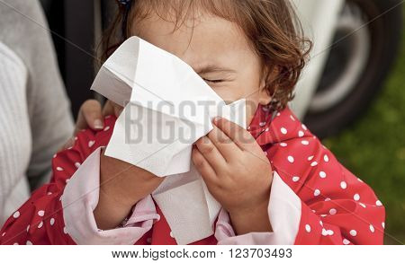 Baby girl dressed with dotted raincoat blowing her nose close to her mother