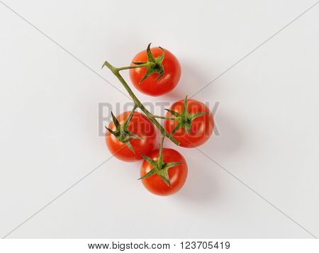 Four cherry tomatoes on vine