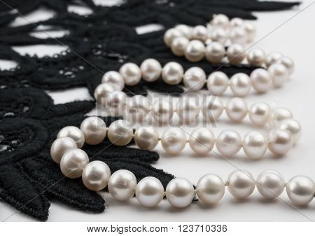 Narrow depth of field pearl necklace and black lace on white