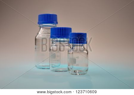 Glass laboratory apparatus isolated on blue table with brown background ** Note: Soft Focus at 100%, best at smaller sizes