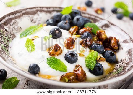 Healthy breakfast, quark with blueberries, pistachios and mint on light wooden background.