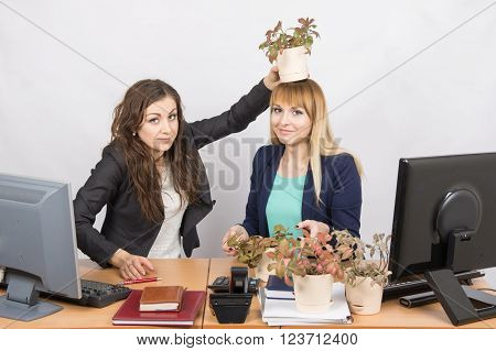 An Employee Of The Office Puts On A Head-grower Colleagues With A Flower Pot