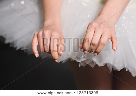 Close-up. hands ballerina on a background of white tutu. Graceful movements of hand. ballerina hands touched to the ballet skirt dress.