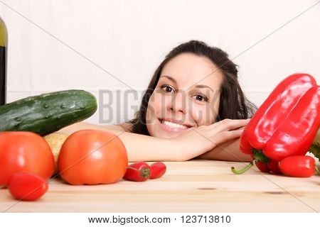 A young woman cutting vegetables in the kitchen.