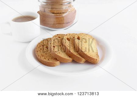 Healthy snack rusk, a type of bread, made from whole-wheat flour, in a plate and a cup of coffee and a bottle containing rusks.