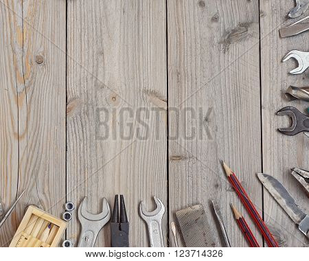 Tools on a wooden floor top view. Empty space for Your text in the center.