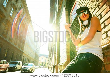 A beautiful young Hip Hop Rapper girl with Headphones in a urban environment. poster