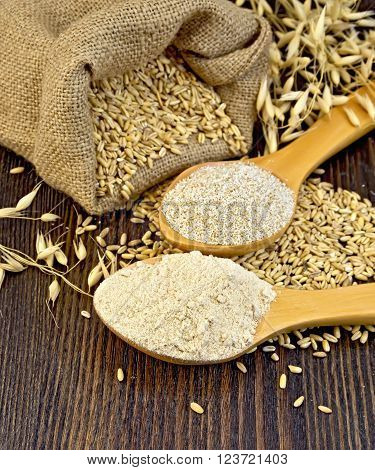 Flour and oat bran in two spoons, bag with oat and stalks of oats on the background of wooden boards ** Note: Shallow depth of field