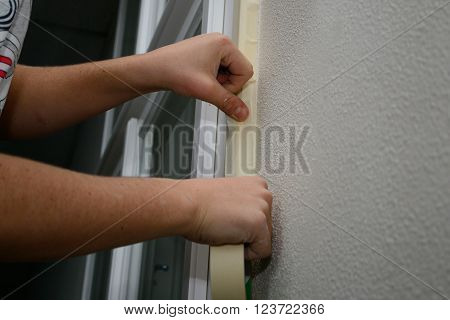 Masking tape to window frames - Person at preparatory work prior to repainting