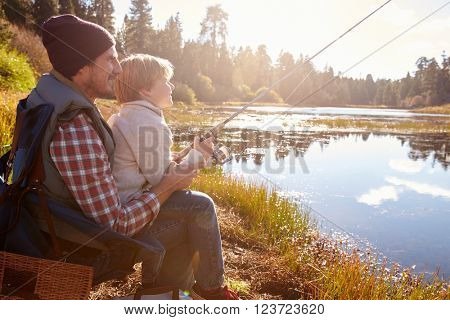 Father teaching son to fish sitting at lakeside
