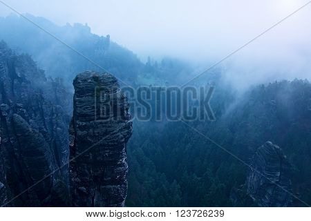 Blue misty landscape mountains. Fantastic dreamy sunrise on rocky mountains with view down to foggy misty valley below