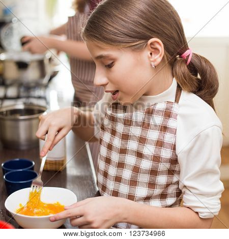 Small Girl In Apron Whisking Eggs In White Bowl