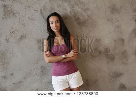 Beautiful girl on a concrete wall background