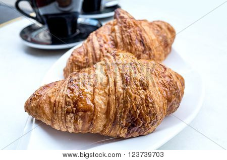 Breakfast with coffee and croissants on table.