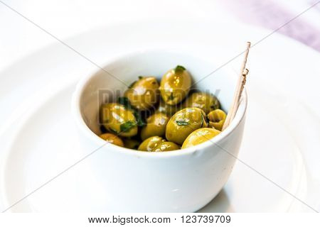 green olives in white bowl on table.