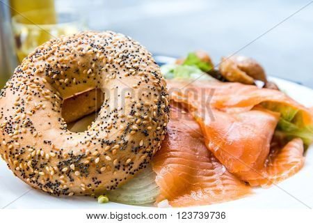 Salmon Bagel with fresh cheese and fresh lettuce on table.