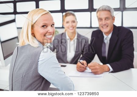 Portrait of happy business people sitting at desk in office