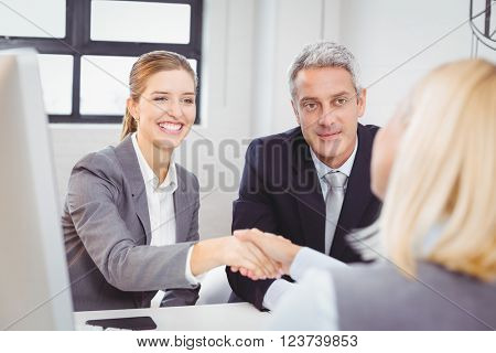 Smart business people handshaking with client in meeting room