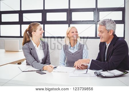 Business people smiling while discussing with client in meeting room