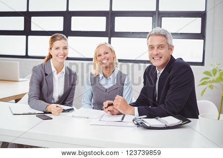 Portrait of happy business people sitting with client at desk in office