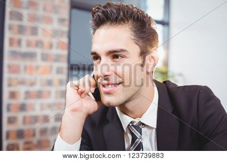 Close-up of smart businessman talking on mobile phone in office