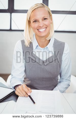 Portrait of happy businesswoman with documents sitting at desk in office