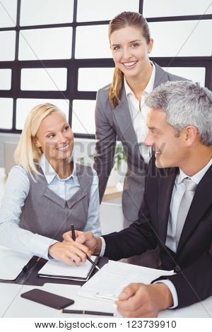 Happy business people with documents at desk in meeting room