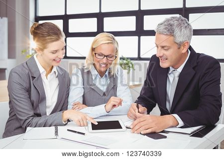 Business people discussing with client over digital tablet at desk in office