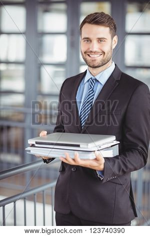 Portrait of happy young businessman with laptop and documents standing at office