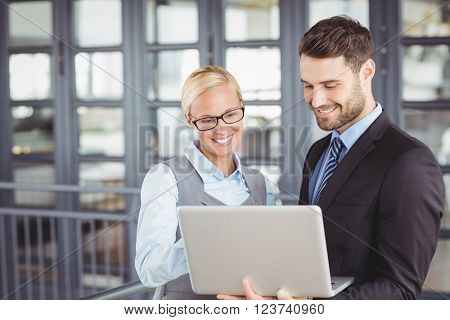 Business people smiling while looking at laptop in office
