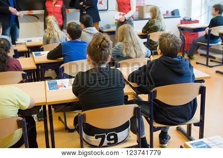 ENSCHEDE NETHERLANDS - MAR 22 2016: Kids of 11 years old sitting behind their desks in a school class.