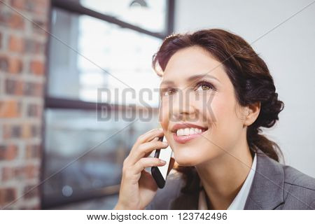 Close-up of happy young businesswoman looking away while talking on mobile phone
