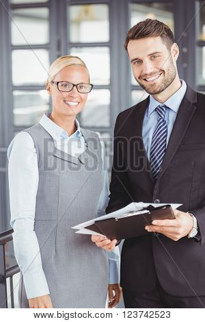 Portrait of happy business people with documents standing in office
