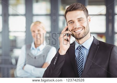 Happy businesman talking on mobile phone while female colleague in background