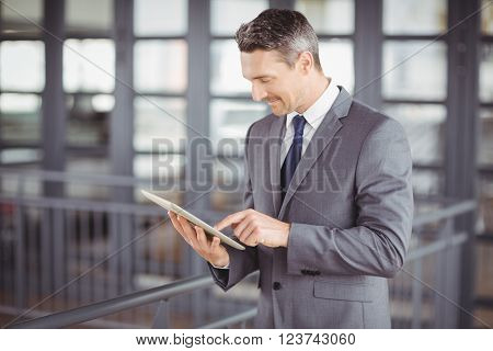 Businessman smiling while using digital tablet in office