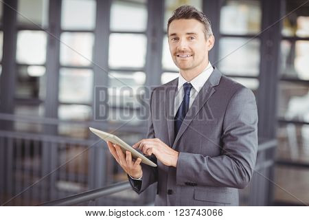 Portrait of happy businessman using digital tablet in office