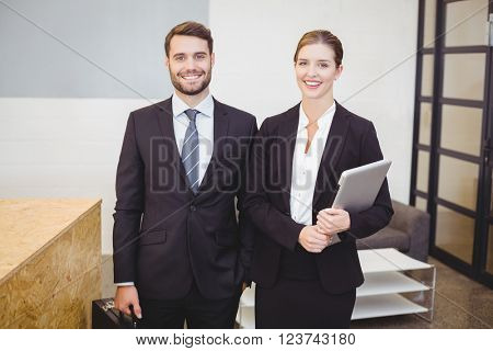 Portrait of happy business people standing by counter in office