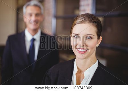 Close-up portrait of female lawyer smiling while male colleague in background